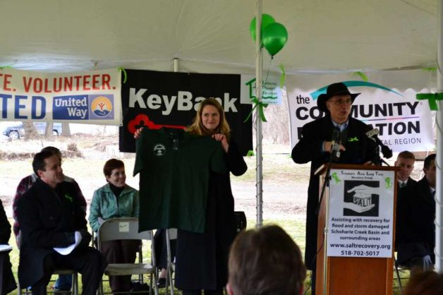 Brian Kaiser (from SUNY Cobleskill, and S.A.L.T. Board member) at the podium speaking, with Rev. Sherri Meyer-Veen (of Schoharie Reformed Church and Chair of S.A.L.T.) next to him holding one of the ?green shirts? which will be worn by volunteers with the Christian Reformed World Relief Committee (greenshirts.org). Listening at left is Assemblyman Peter Lopez.