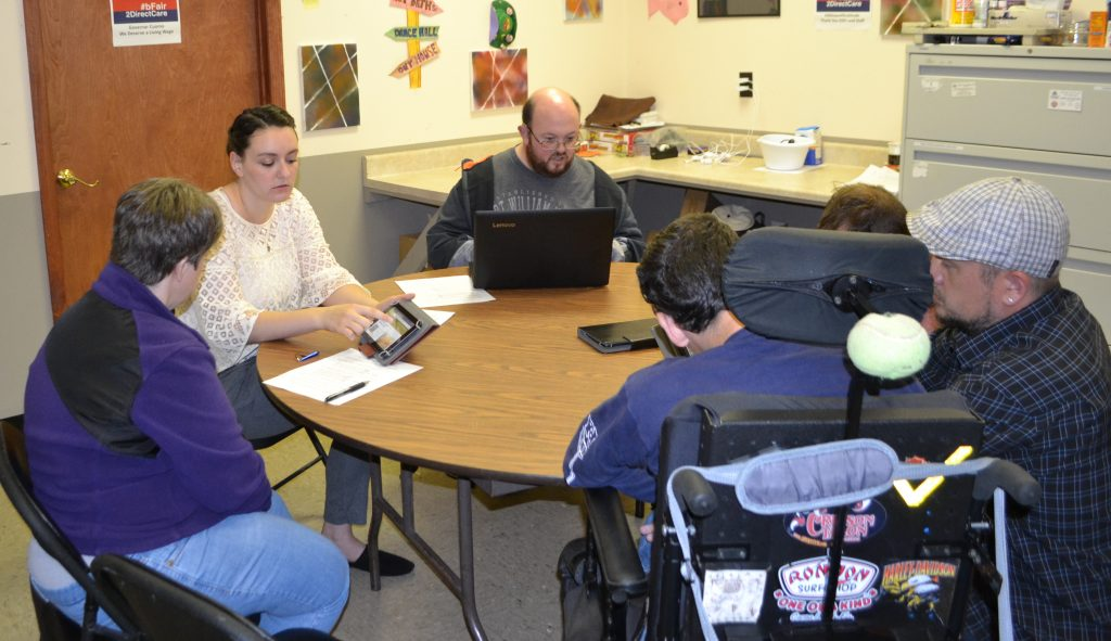 Project coordinator Sarah Roberts sits at a round table with four ARC participants and one ARC staff member. gets feedback from ARC participants at the first interactive session on website accessibility at the Schoharie ARC.